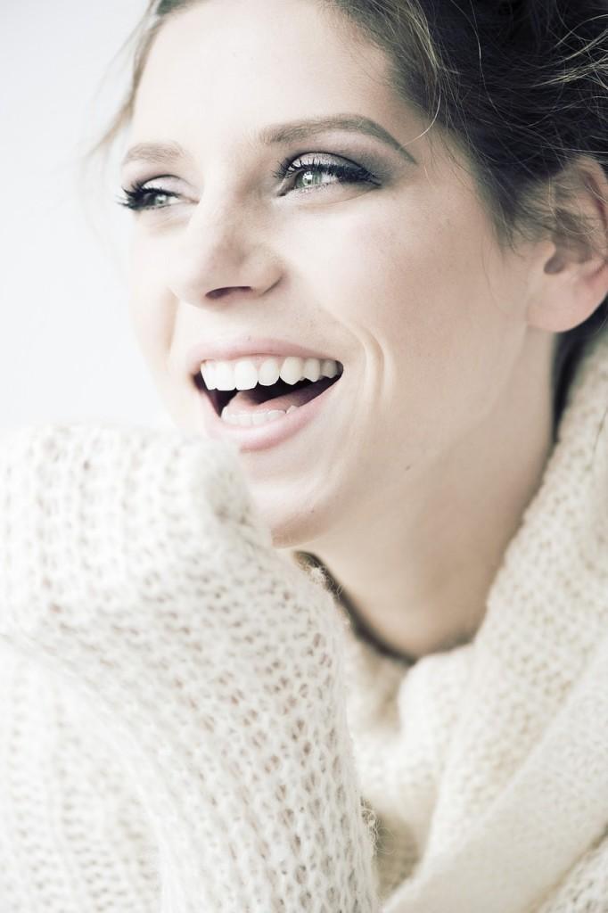 blog-strahlend-weiße-zaehne-frau-lacht-weißer-pullover-