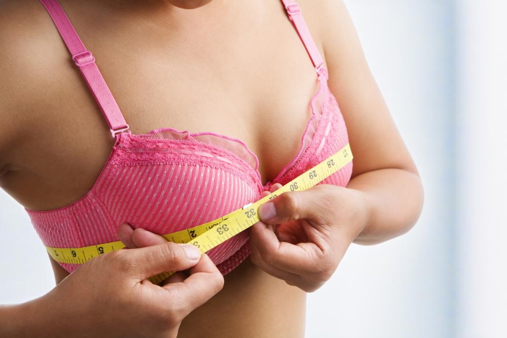 Frau misst Busenumfang für mögliche Brustvergrößerung