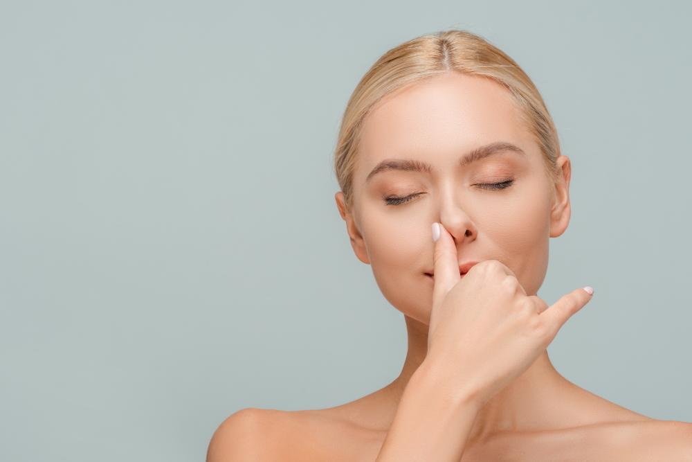 Frau fässt sich an die Nase nach Nasen-OP